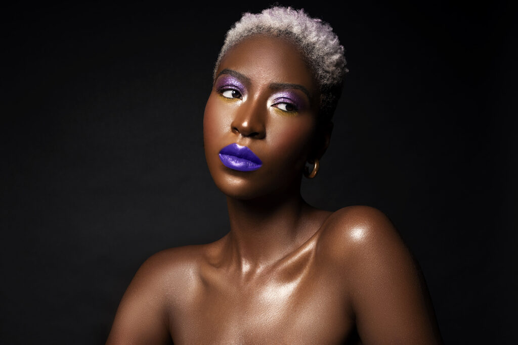 Model posing with bright purple lipstick